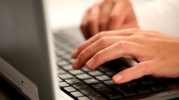 stock-footage-hands-typing-on-a-laptop-keyboard